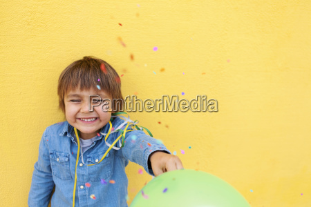 smiling little boy with green balloon