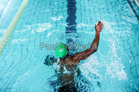 fit man swimming in the pool
