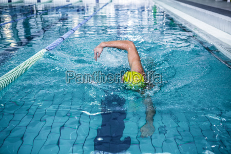fit man swimming with swimming hat