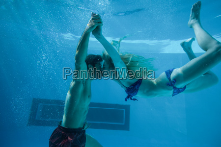 cute couple kissing underwater in the