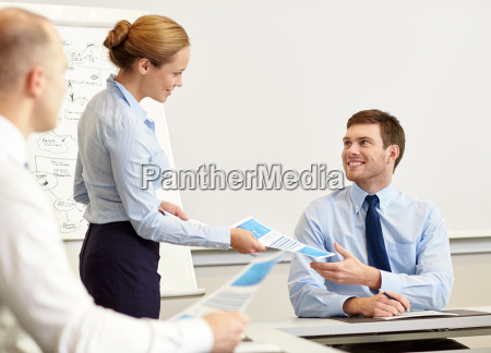 smiling woman giving papers to man