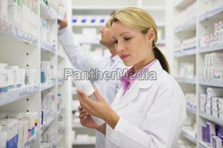 pharmacist reading bottle of prescription medication
