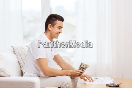man with papers and calculator at