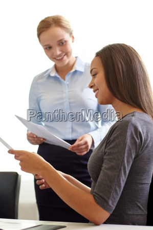 smiling businesswomen with papers in office