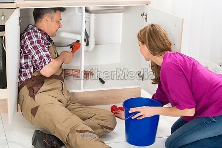 male plumber repairing pipe under sink