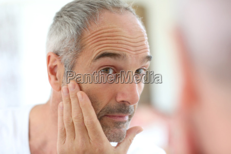 mature man in front of mirror