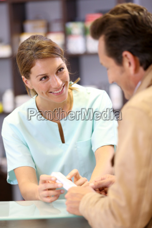 pharmacist giving advice to customer on