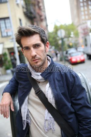 casual guy crossing shopping street in