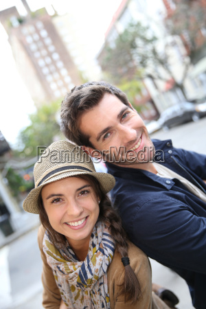 cheerful couple standing in shopping street