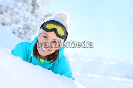 cheerful girl in ski outfit laying