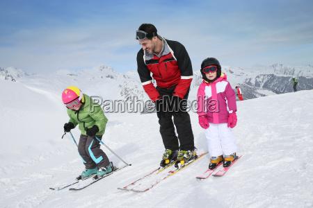 ski teacher helping young kids to