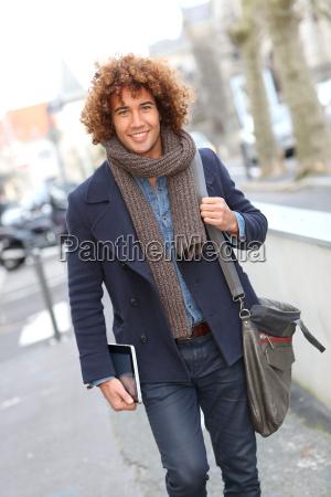 smiling handsome guy walking in street