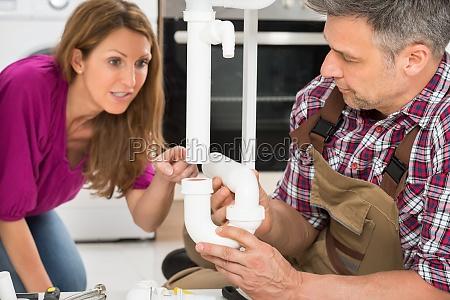 plumber repairing pipe of sink