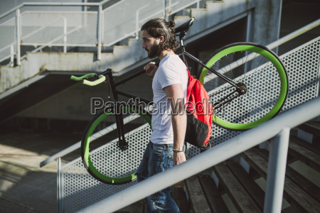 young man carrying fixie bike on