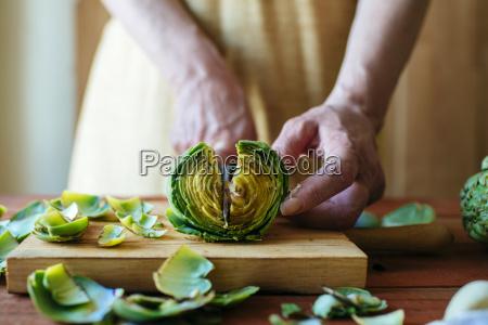 womans hands cutting an artichoke close