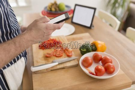 man using smartphone while preparing food