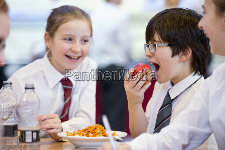 smiling middle school students eating lunch