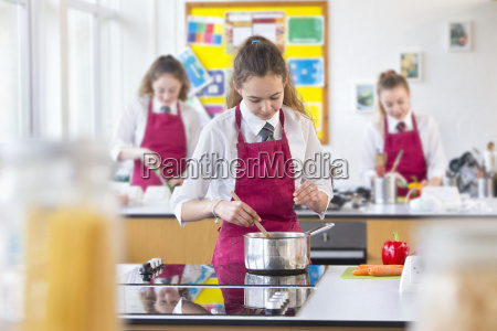 high school student cooking in home