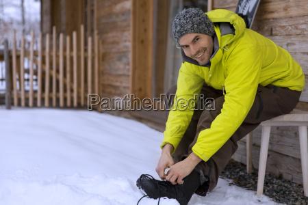 man adjusting boot in snow portrait