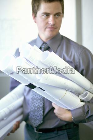 portrait of a businessman holding several