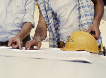 businessman and construction worker discussing plans