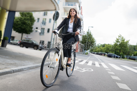 businesswoman with handbag riding bicycle