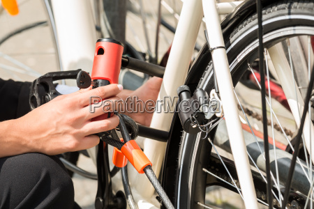 businesswomans hand locking up her bicycle