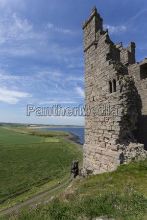 ruins of dunstanburgh castle overlooking fields