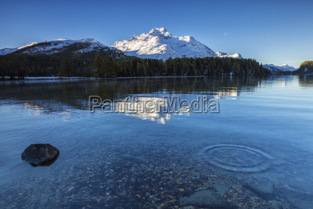 dawn illuminates the snowy peaks reflected
