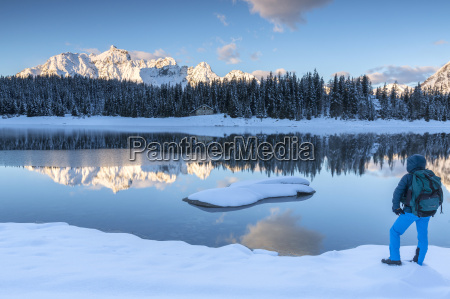 hiker admires the snowy peaks and