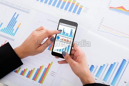 businesswoman analyzing financial graphs using smartphone