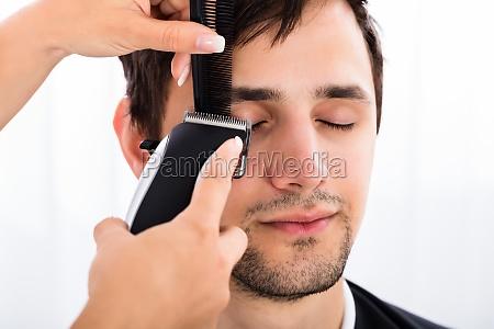 close up of a hairdresser cutting