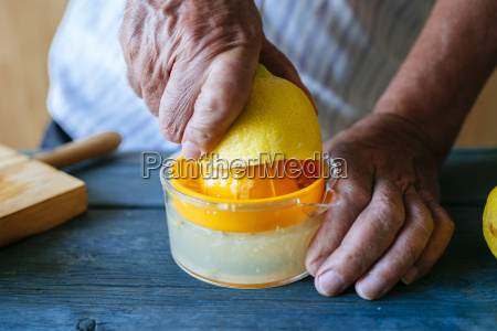 close up of hands squeezing lemon