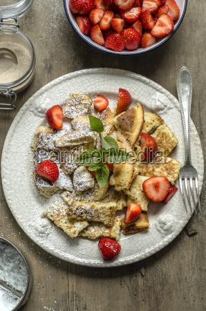 kaiserschmarrn with fresh strawberries cinnamon powdered