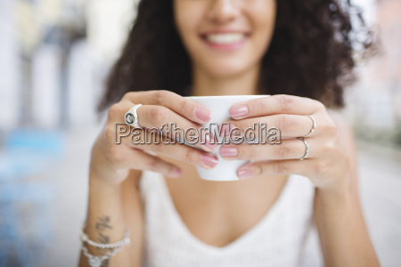 hands of young woman holding cup