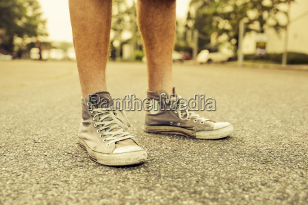 mans feet with old sneakers close