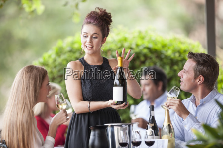 waitress showing wine bottle to clients