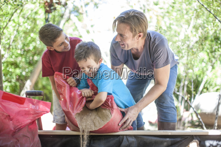 father and sons filling sand into