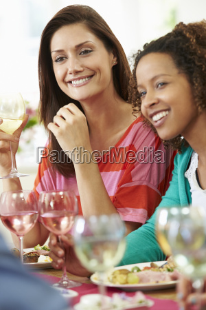 two women relaxing at dinner party