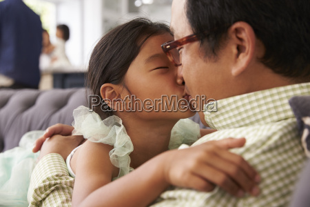 affectionate father and daughter relaxing on