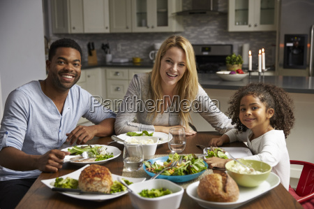 girl and mixed race parents dine