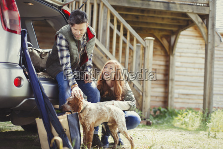couple with dog at back of