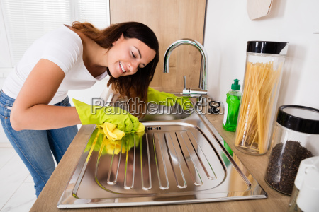 woman cleaning stainless steel sink