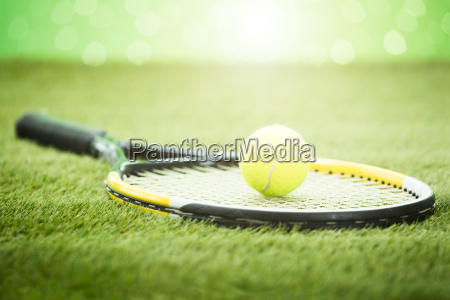 tennis racket with ball on grass