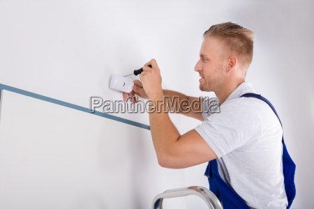 man installing motion detector for security