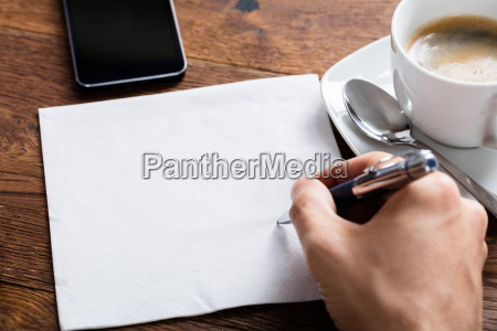 person hand holding pen on white