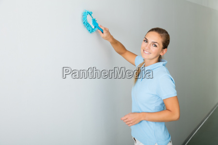 woman cleaning the ceiling with mop