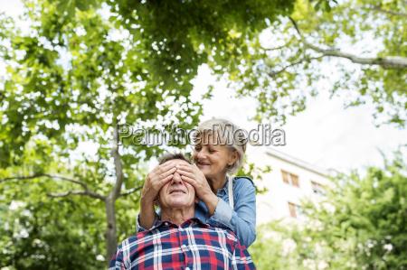 senior woman covering husbands eyes
