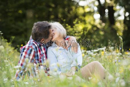 senior couple kissing on a meadow