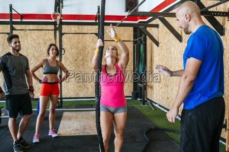 group of athletes watching woman climbing